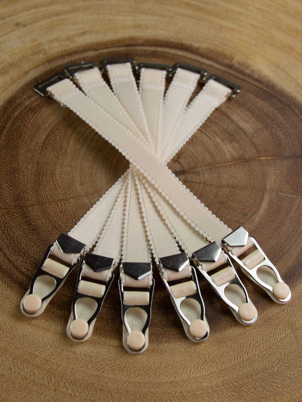 6 Adjustable beige garter suspenders for stockings with silver metal accents.