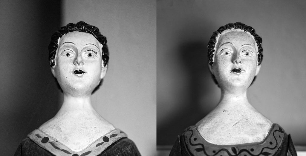 Black and white portraits of two antique wooden dolls found in an old southern house