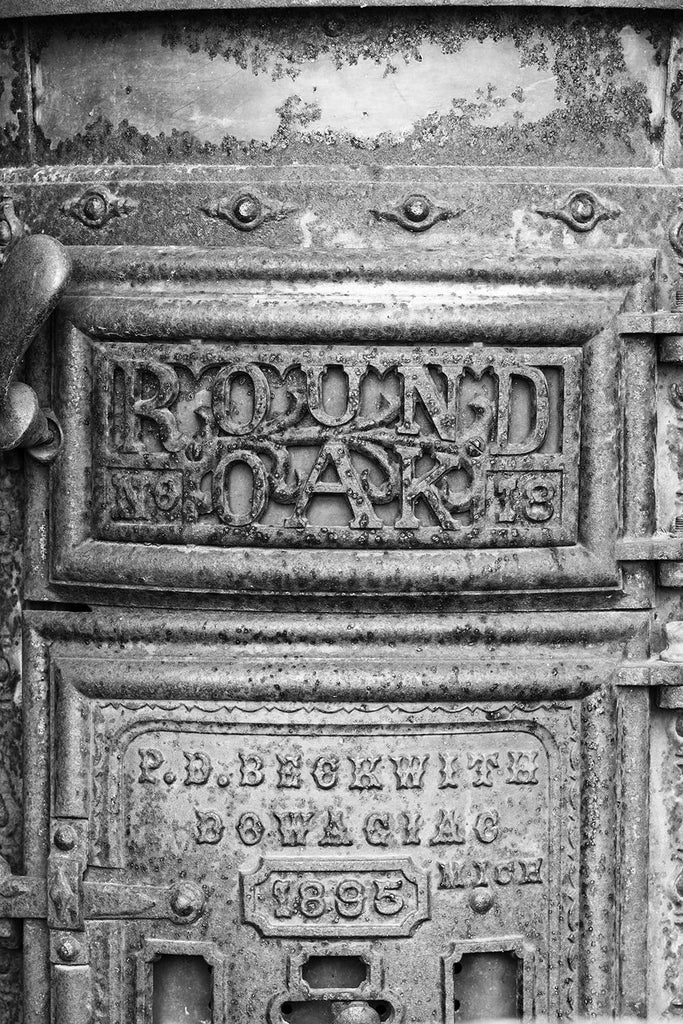 Black and white photograph of a rusty, antique Round Oak stove found in a collapsed building