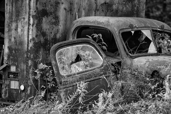 Broken-down truck in the tall grass and weeds, a black and white photograph by Keith Dotson.