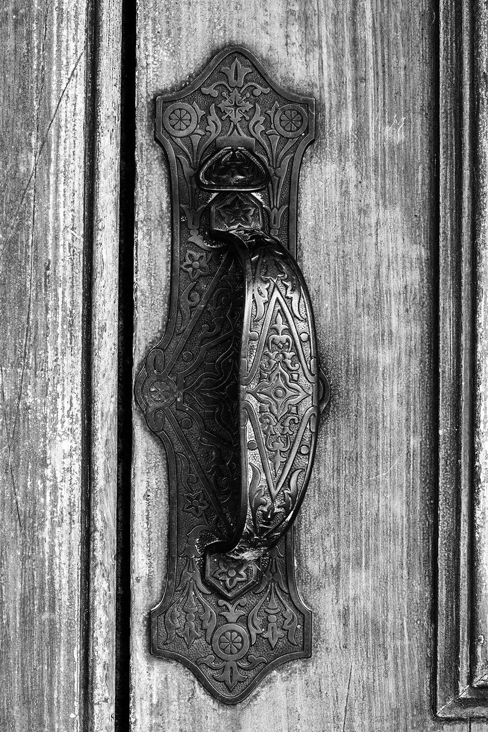 Black and white architectural detail photograph of an ornately detailed old door pull on the door of an 1880s-era library building. Buy a fine art print.