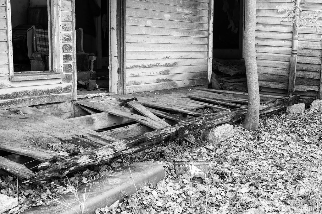 Broken porch of abandoned farmhouse. Black and white photograph by Keith Dotson.