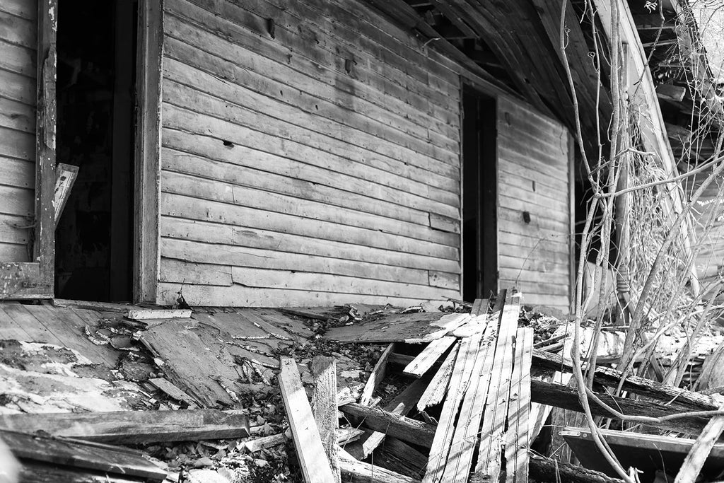 Collapsing back porch of an abandoned farmhouse. Black and white photograph by Keith Dotson.