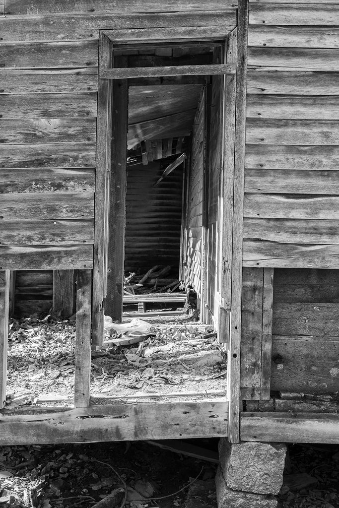 Row of door frames on the abandoned farmhouse. Black and white photograph by Keith Dotson.
