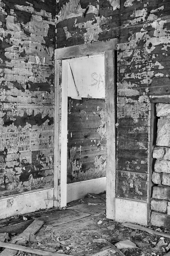 Interior photograph of the abandoned farmhouse. Notice the scraps of newspaper and wallpaper on the walls. Black and white photo by Keith Dotson.