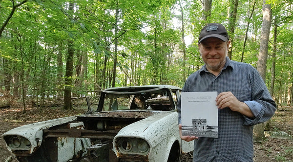 Portrait of photographer Keith Dotson holding his book Unloved and Forgotten: Fine Art Photographs of Abandoned Places