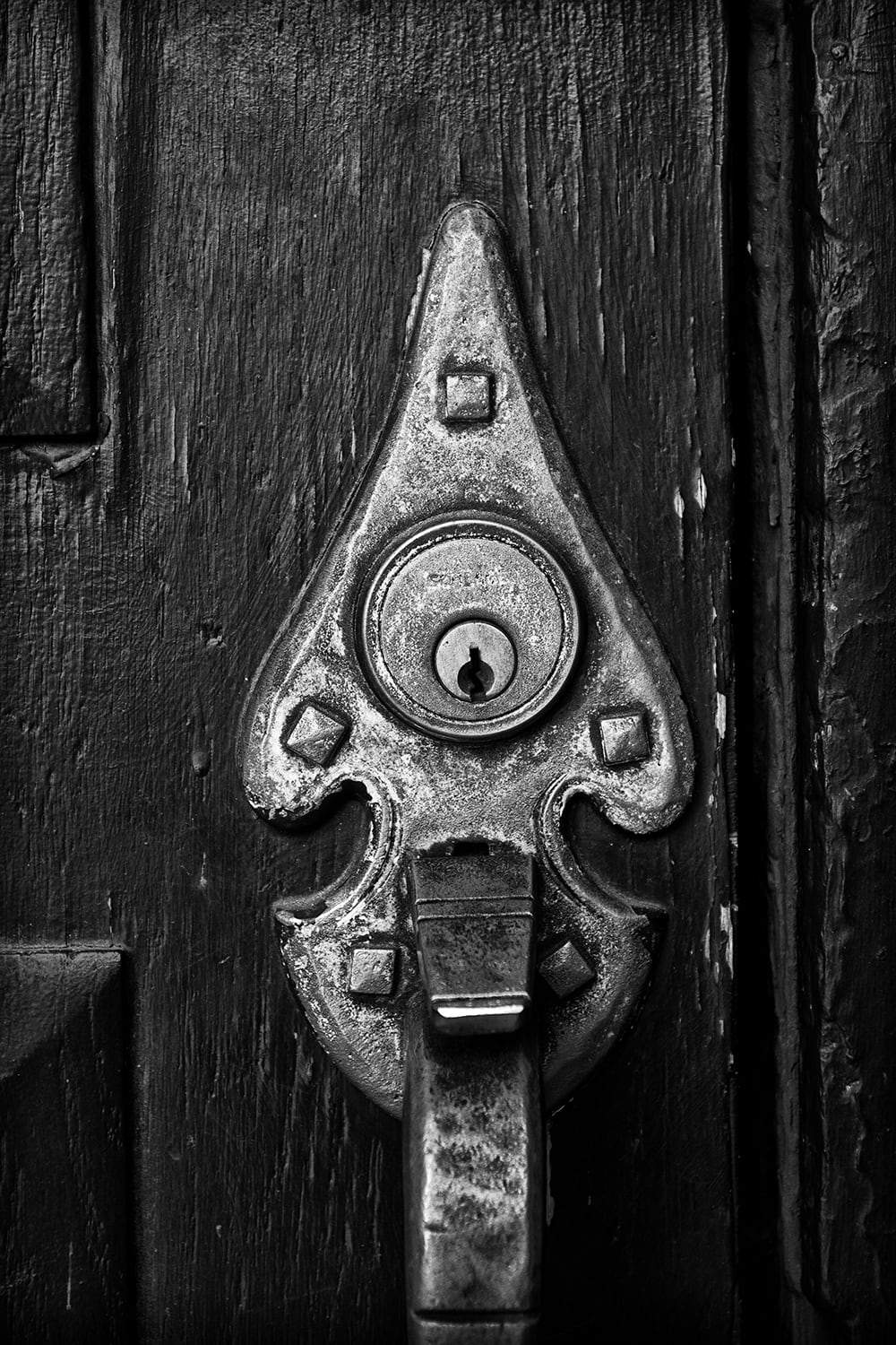 Black and white architectural detail photograph of an old brass door handle on a textured black door in Madison, Wisconsin. Buy a fine art print here.