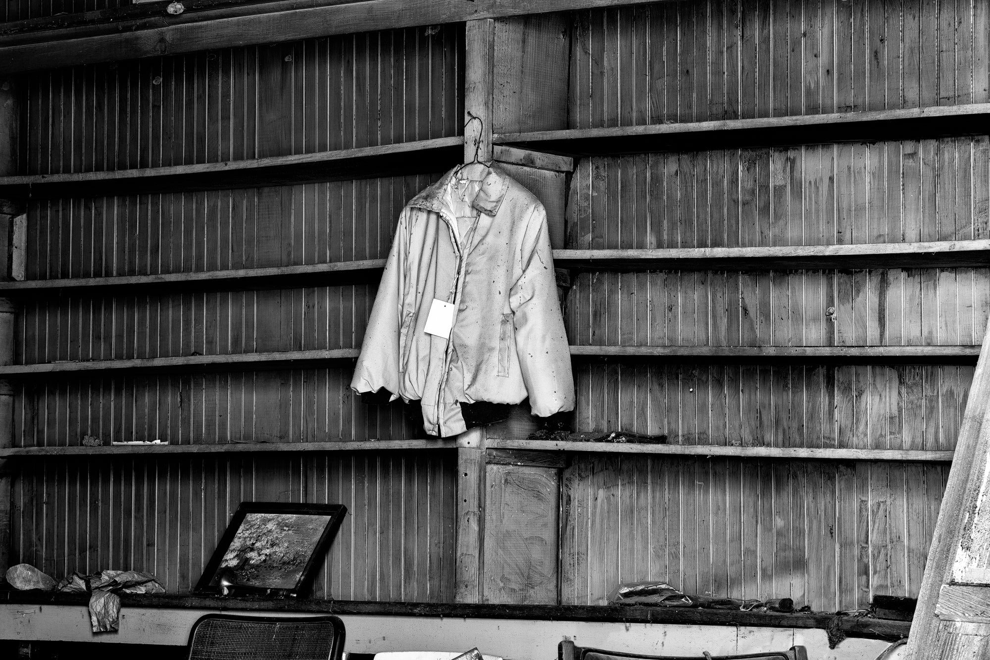 Blue Jacket with Sale Tag Hanging in an Abandoned Old Country Store. Black and White Photograph by Keith Dotson. Click to buy a fine art print.
