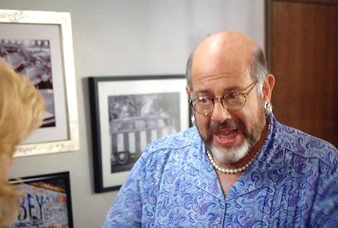 In this scene, the photo is seen over the shoulder of Maria's agent, Bruce, played by Fred Melamed.