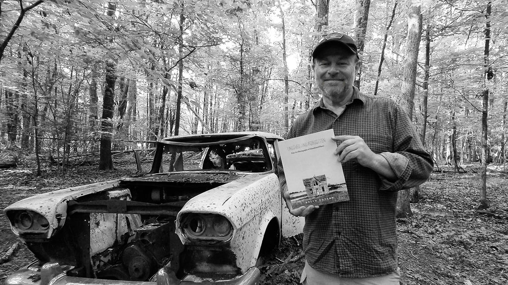 "Portrait of fine art photographer Keith Dotson holding his new book, ""Unloved and Forgotten: Fine Art Photographs of Abandoned Places."""
