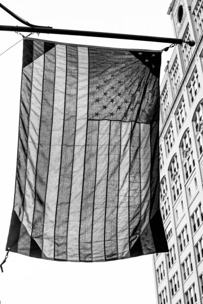 A US flag suspended downtown, a black and white photograph by Keith Dotson. Click to buy this photo.