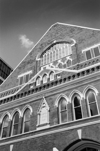 "Black and white photograph of Nashville's famous Ryman Auditorium, the ""mother church of country music,"" which begin as a tabernacle, and later served as home to the home of the Grand Ol' Opry. Today, it's one of the county's most venerated concert venues."