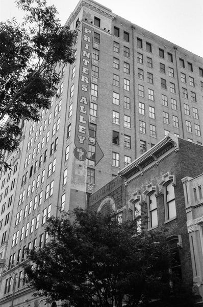 Black and white photograph of a tall Printer's Alley sign painted onto the sign of a building in Nashville.