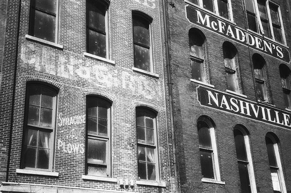 Black and white photograph of antique painted signs on the old brick walls of Nashville's riverfront. The turn-of-the-century sign for Syracuse Plows can be seen at bottom left.