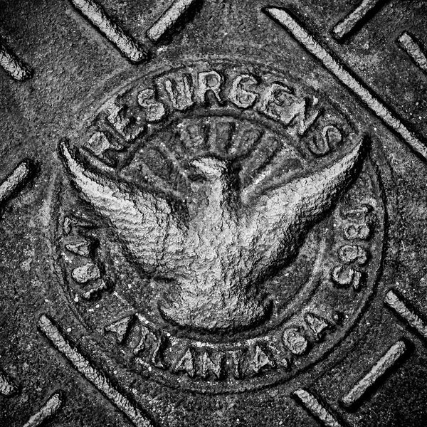 Black and white photograph Atlanta's Resurgens phoenix icon casy into a heavy iron man hole cover.