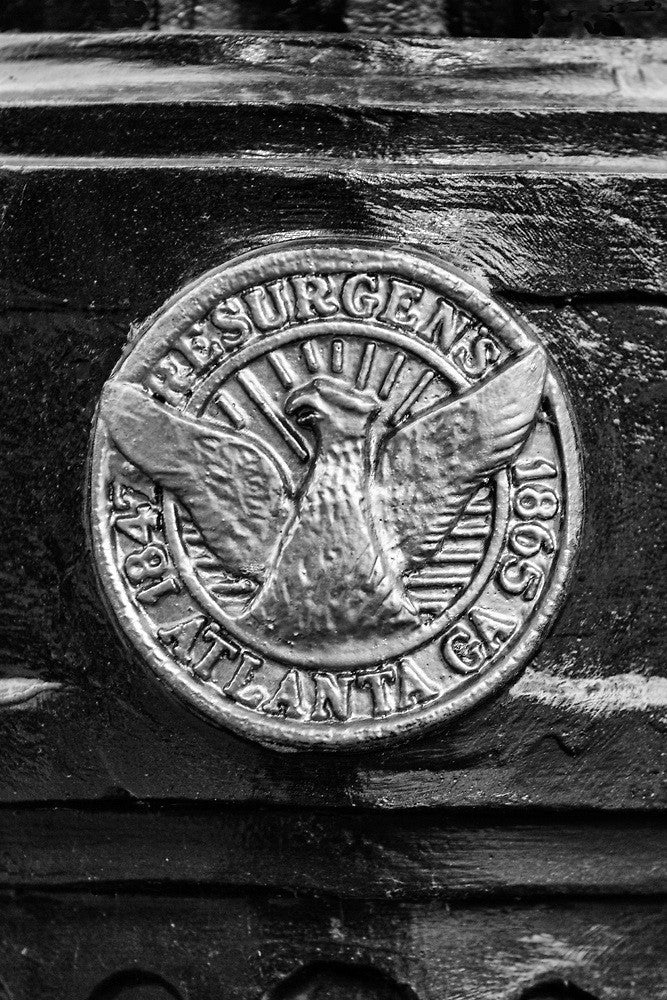 "Black and white photograph of Atlanta's Resurgens logo as seen on a light post. Resurgens roughly translates to ""rise again,"" remembering when Atlanta had to rebuild from the ashes of the Civil War."