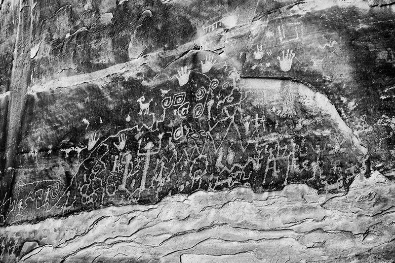 Black and white fine art photograph of ancient petroglyphs that can still be seen at Mesa Verde, Colorado. Petroglyphs are images made by scratching or carving into stone. These glyphs tell the origin story of the Pueblo people.