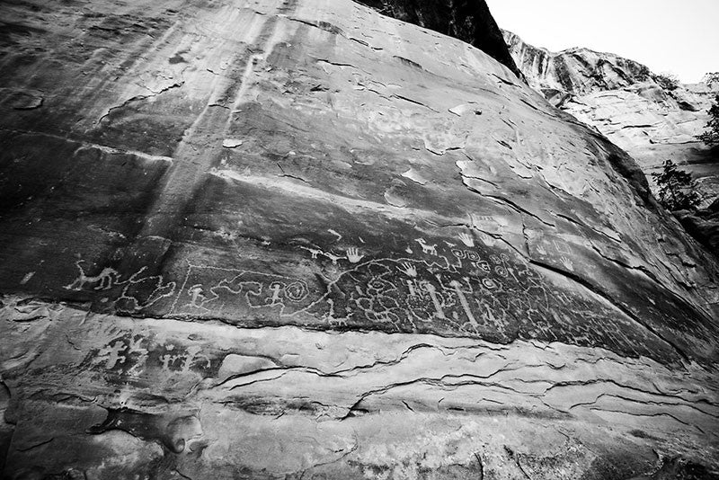 Black and white fine art photograph of ancient petroglyphs that can still be seen at Mesa Verde, Colorado. Petroglyphs are images made by scratching or carving into stone. These glyphs tell the origin story of the Pueblo people. This photograph makes the glyphs appear high on the wall, but in actuality, the glyphs were within reach using a narrow stone ledge just below the wall.