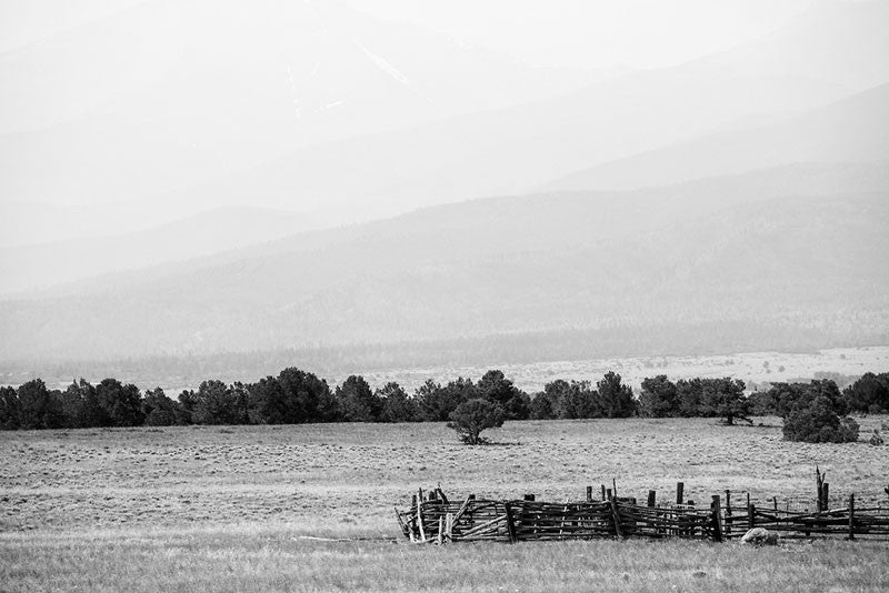 Black and white fine art landscape photograph of hazy Colorado mountains in the background, with an abandoned collapsing corral in the foreground.