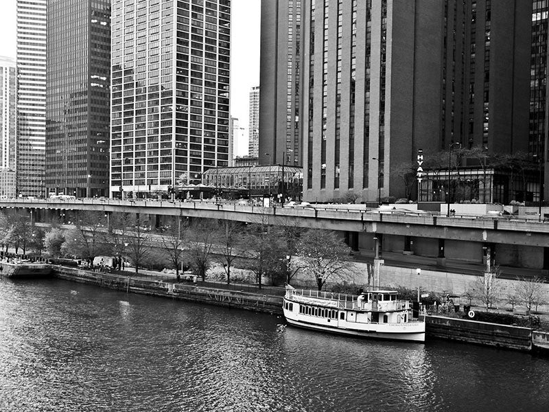 Black and white photograph of a boat on the Chicago River, dwarfed by skyscrapers in downtown Chicago.