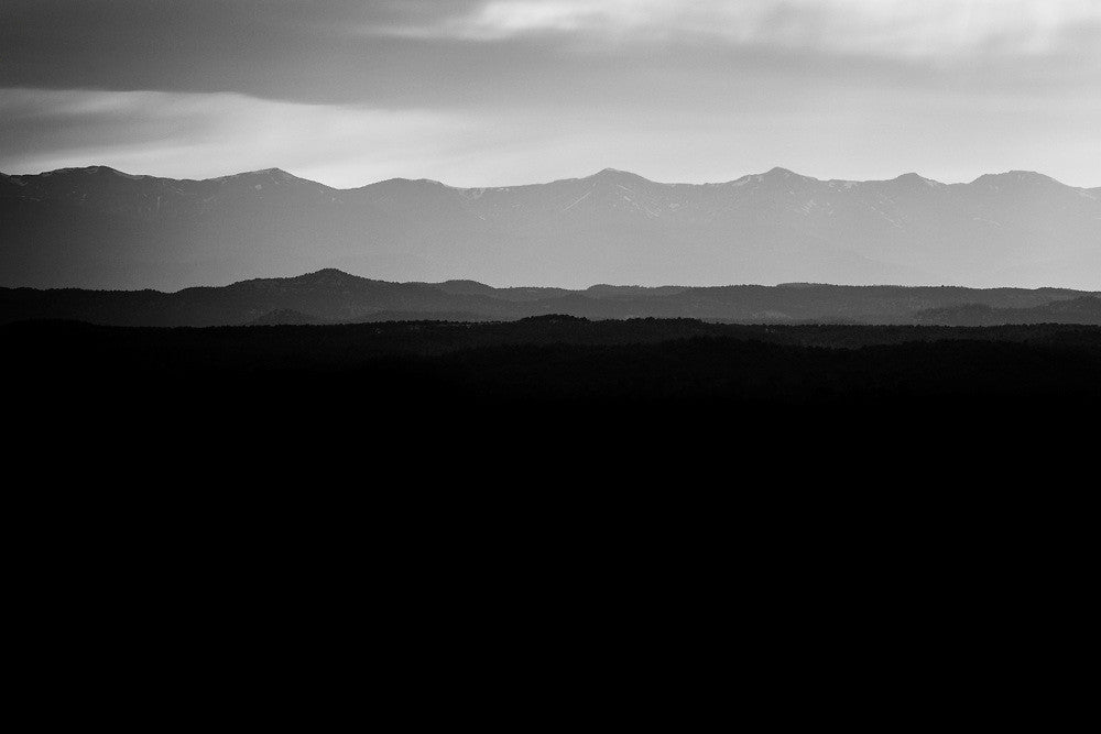 Black and white fine art landscape photograph of hazy Colorado mountains in early morning light.