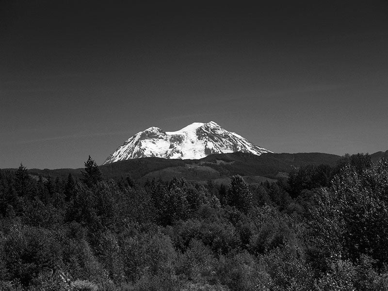 Black and white photograph of Mt. Rainier gleaming white against a deep blue Pacific Northwest sky.