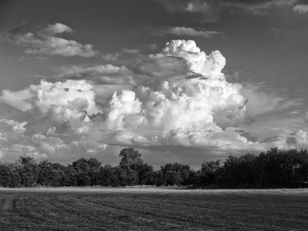 Black and white landscape photograph of brewing storm clouds rising over a farmer's field, near Georgetown, Texas.