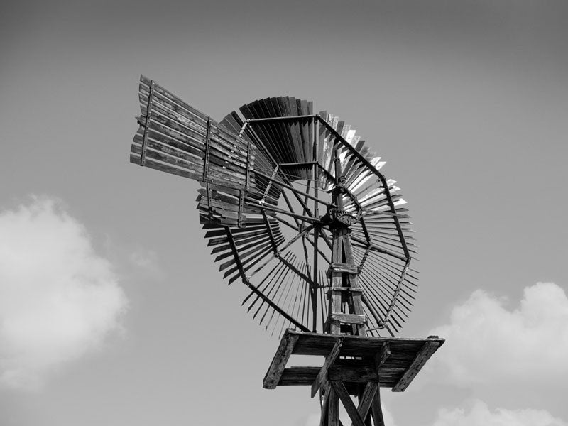 Black and white photograph of a historic wooden windmill in the desert of west Texas near Pecos.