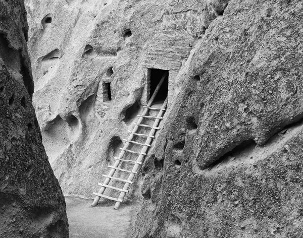Black and white photograph of a wooden ladder that leads to ancient cliff dwellings at Bandelier National Monument in New Mexico.