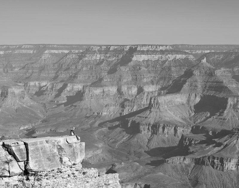 Black and white landscape photograph of the south rim of the Grand Canyon just after sunrise, with a guy sitting on the point of a precipice on the edge.