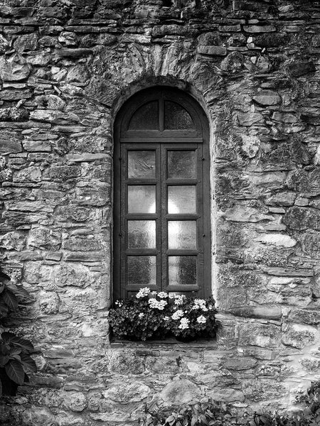 Black and white architectural photograph of the chapel window of an old Spanish mission, built in the 1500s, in San Antonio, Texas.