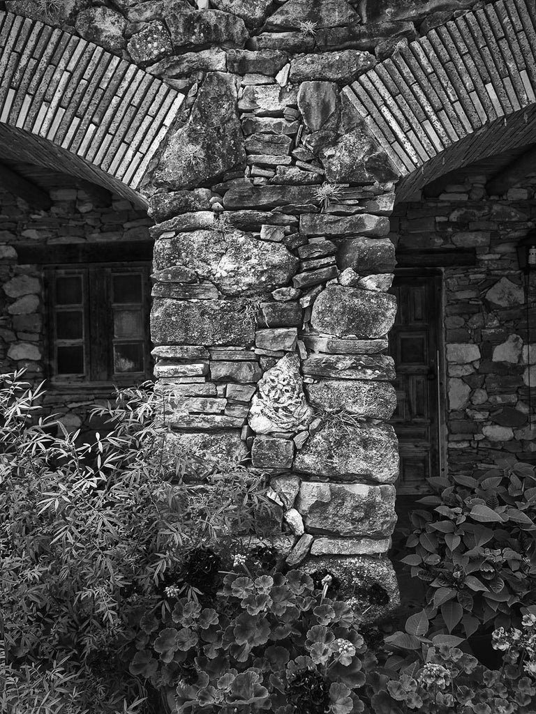 Black and white architectural photograph of the rustic limestone arches at the old Spanish Mission Espada, built in the 1700s, in San Antonio, Texas.
