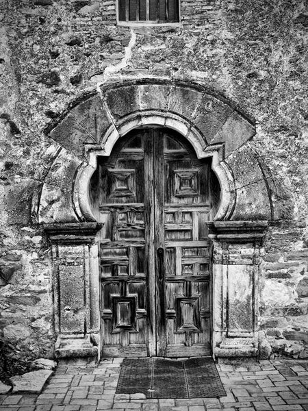 Black and white architectural photograph of the carved wooden front doors of the old Spanish Mission Espada, built in the 1500s, in San Antonio, Texas.