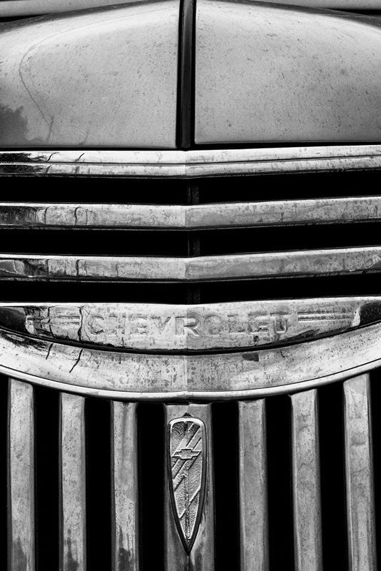 Black and white fine art photograph detail of the hood and chrome grill of a vintage 1947 Chevrolet.