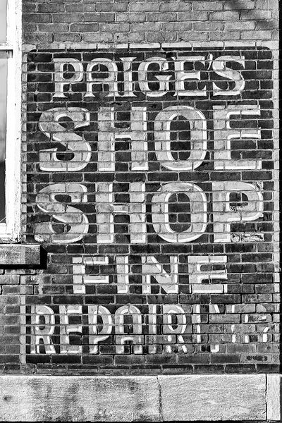 "Black and white photograph of a historic painted ""ghost ad"" for the now defunct Paige's shoe shop seen on a brick wall in Hopkinsville, Kentucky."