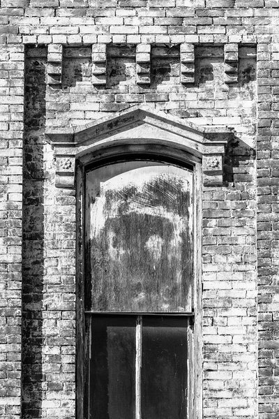 Black and white photograph of a window on an abandoned brick building with a stone pediment and paint peeling from its bricks.