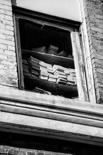 Black and white photograph of a window on the second floor of an abandoned building that shows stacks of paperback books on shelves.