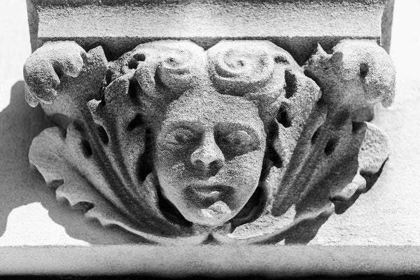 Black and white photograph of female cherub face centered amongst leaves carved in stone on a building constructed in 1902. Originally built for a regional telephone and telegraph company, the building later became a lodge for the International Order of Odd Fellows (I.O.O.F).