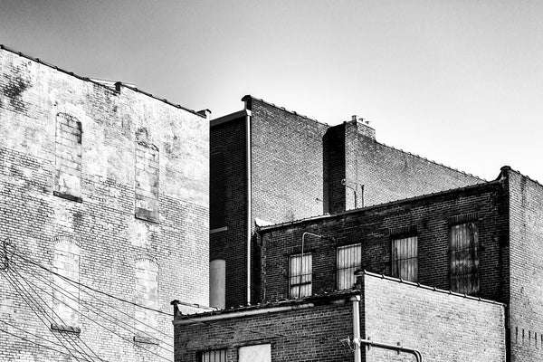 Black and white photograph of old brick buildings in a small town shot in bright afternoon sun. Hopkinsville Kentucky.
