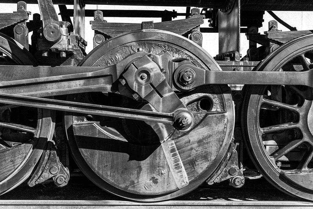 Black and white photograph of the wheels of an old locomotive on the tracks.