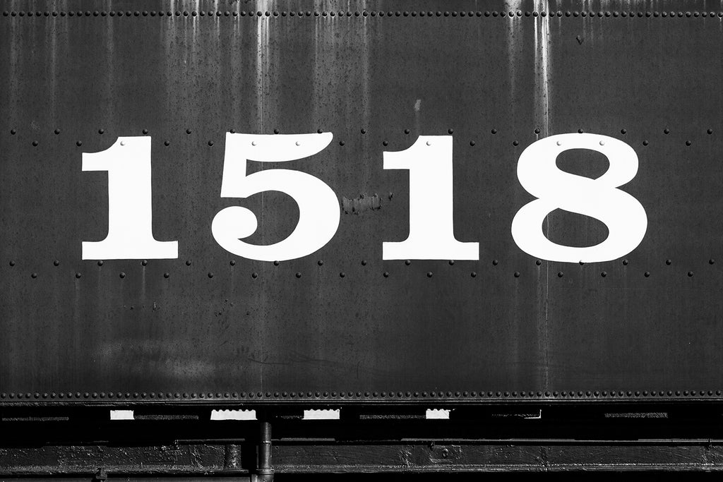 Black and white photograph of the side of an old railroad car displaying the large numbers 1518.