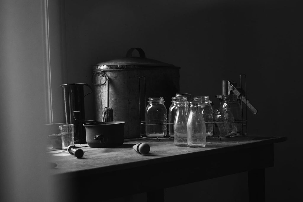 Black and white photograph of Bell jars and pots in the kitchen of a very old house shot in natural light