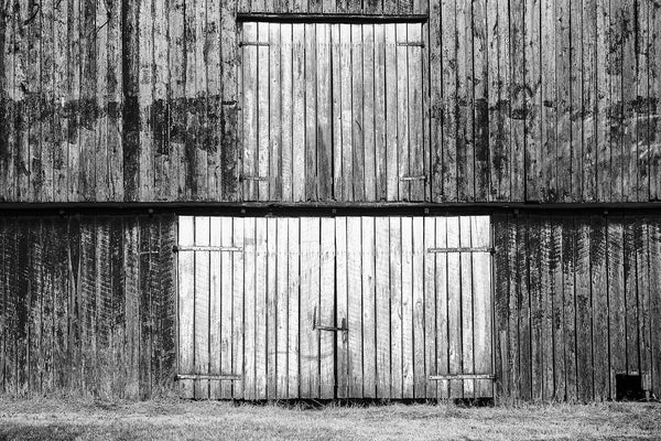 Black and white photograph of barn doors on the first and second levels of a big old weather-beaten red barn. This photograph is composed flatly, allowing the rectangles and vertical lines to create an almost abstract architectural image.