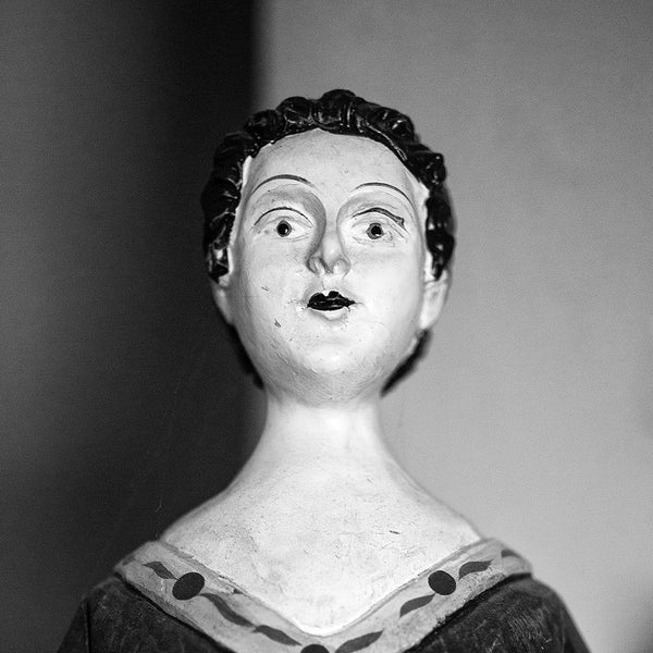 Black and white photograph of an antique wooden doll figurine found in an old house, photographed portrait style. (Square format)