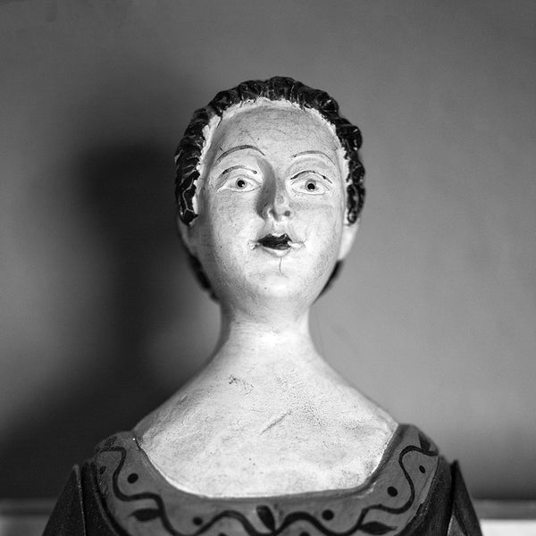 Black and white photograph of an antique wooden doll with hand-painted features found in an old house, photographed portrait style. (Square format)