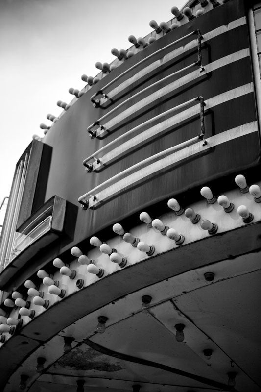 Black and white photograph of a vintage theater marquee in a small town, showing rows of light bulbs and curving neon.
