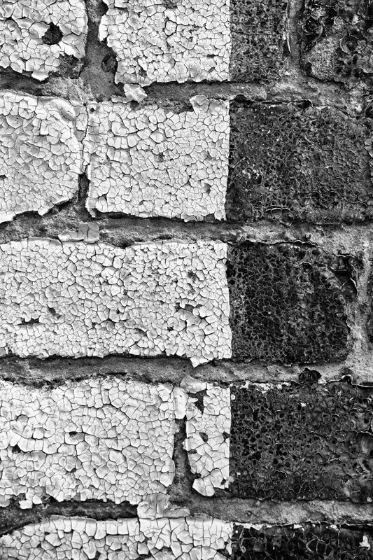 Black and white detail photograph of paint chipping and peeling from old bricks on a small town building.