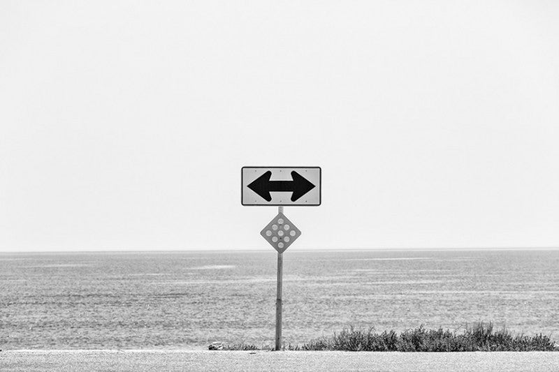 Black and white ladnscape photograph of the Florida coastline, with a road sign as a focal point.