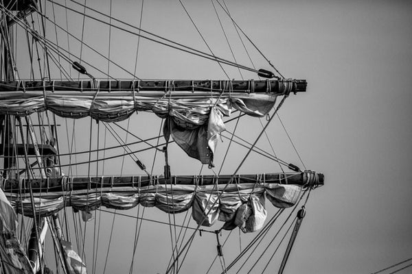 Black and white detail photograph of the masts, rigging, ropes, and sails of a tall sailing ship in St. Augustine, Florida.