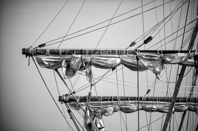 Black and white detail photograph of the rigging of the ropes and sails of an old sailing ship in St. Augustine, Florida.